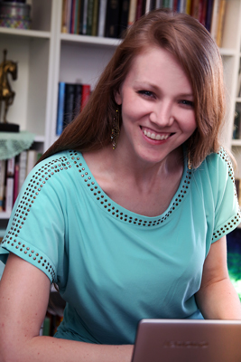 Portrait of Norma Sue O'Neil in a turquoise shirt with books in the background